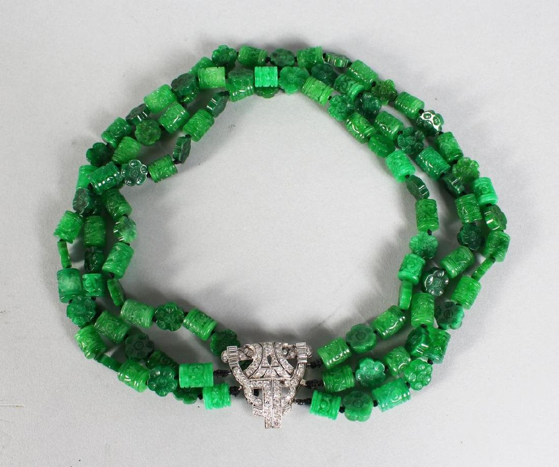 A THREE ROW JADE NECKLACE with ART DECO DIAMOND CLASP.