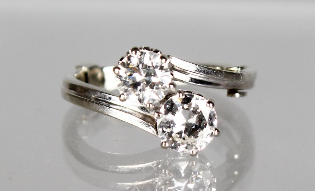 A SUPERB TWO STONE DIAMOND CROSSOVER RING in 18ct white