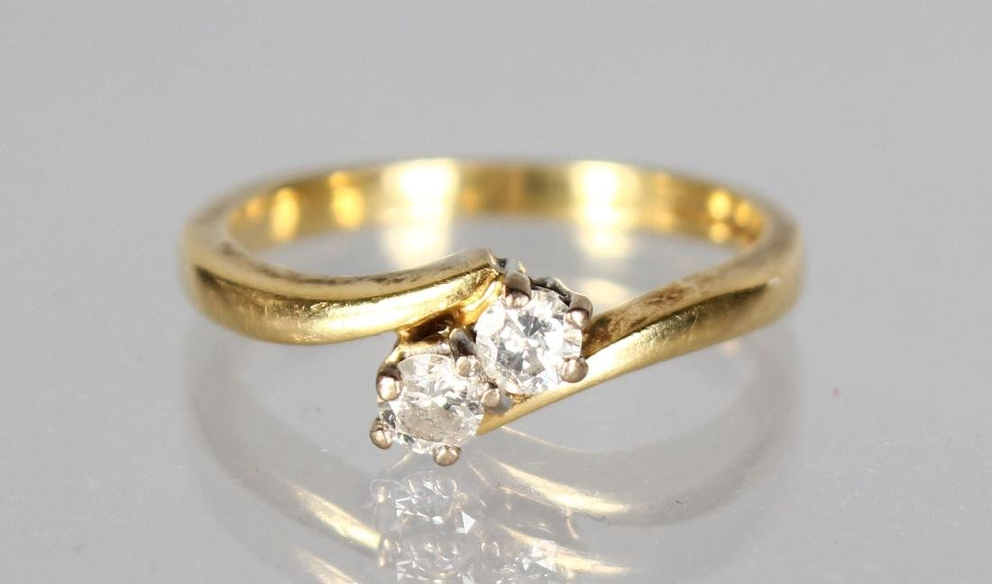 AN 18CT GOLD AND DIAMOND CROSSOVER RING.