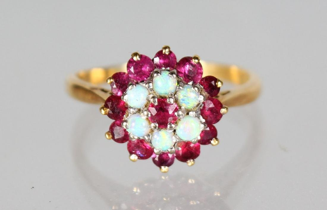 AN 18CT GOLD, RUBY AND DIAMOND CLUSTER RING.