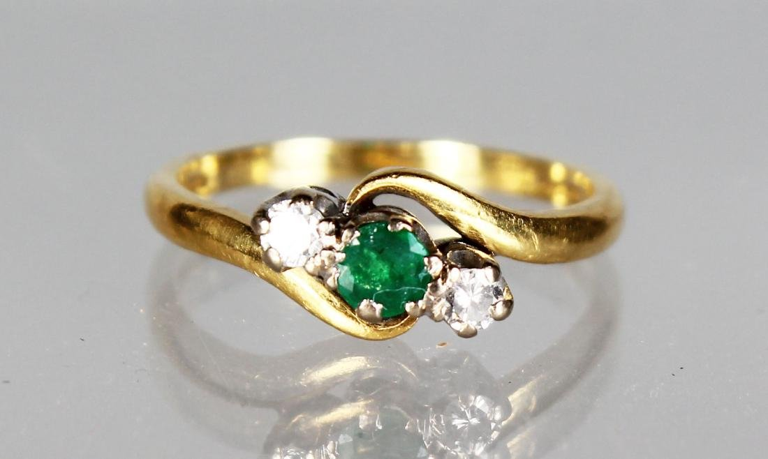 AN 18CT GOLD, DIAMOND AND EMERALD CROSSOVER RING.