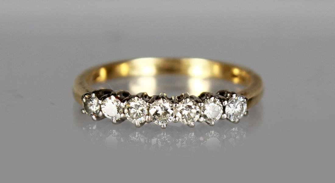 A SEVEN STONE DIAMOND AND GOLD RING.