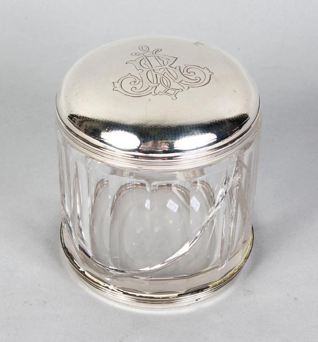 A GLASS CIRCULAR POT with silver top.