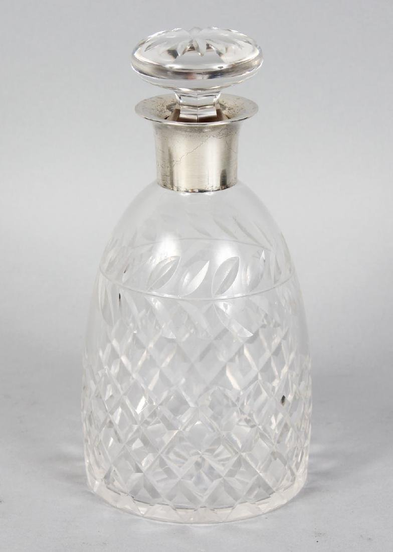 A CUT GLASS DECANTER AND STOPPER with silver band.