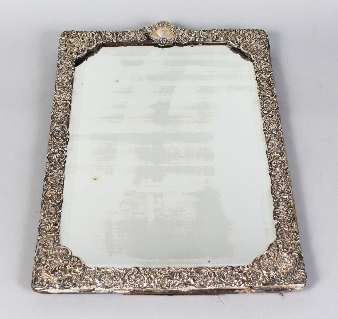 A LARGE UPRIGHT EASEL MIRROR with repousse foliate