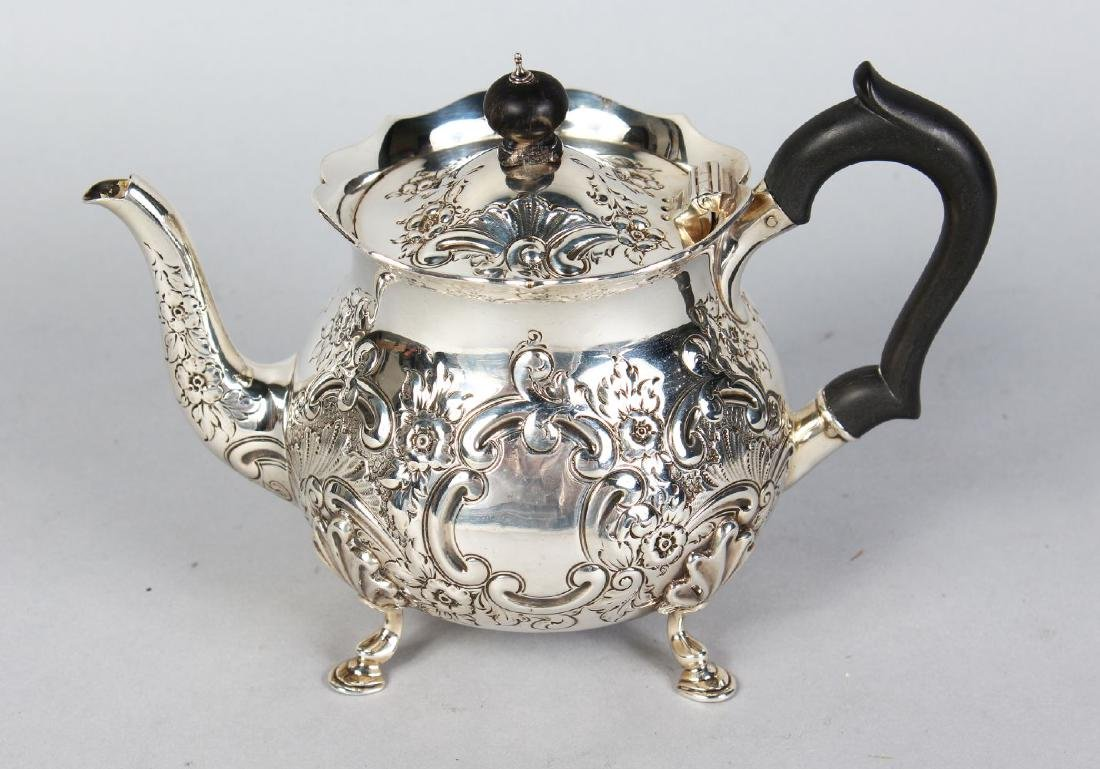 A TEAPOT with repousse decoration, ebony handle and