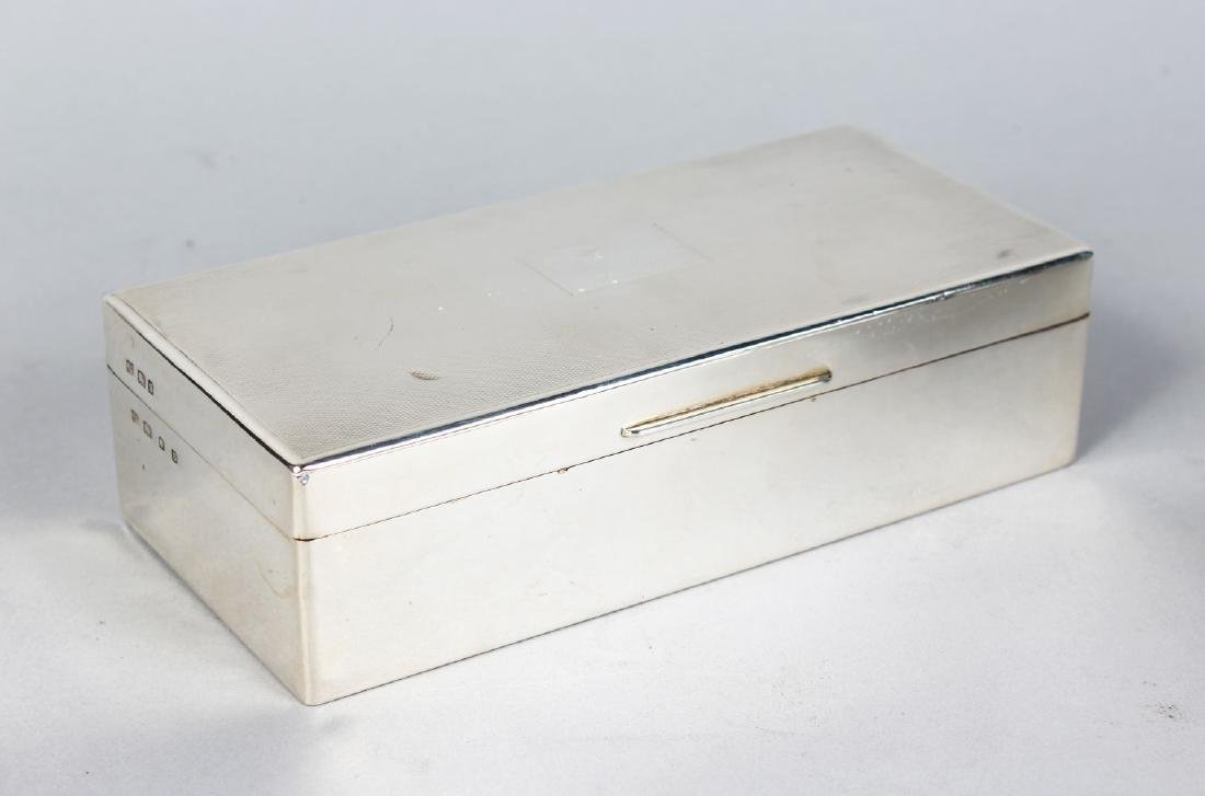 A RECTANGULAR SILVER CIGARETTE BOX, with engine turned