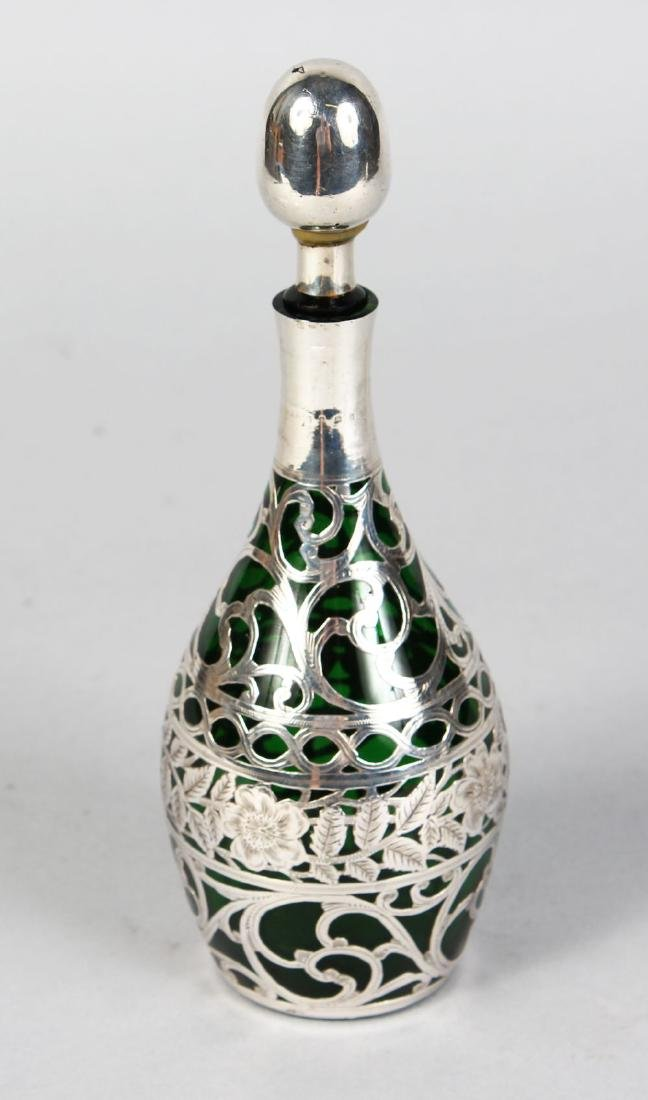 A SILVER MOUNTED GLASS PERFUME BOTTLE AND STOPPER.
