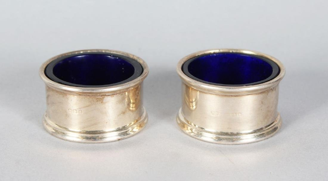 A PAIR OF CIRCULAR SALTS with sapphire blue liners.