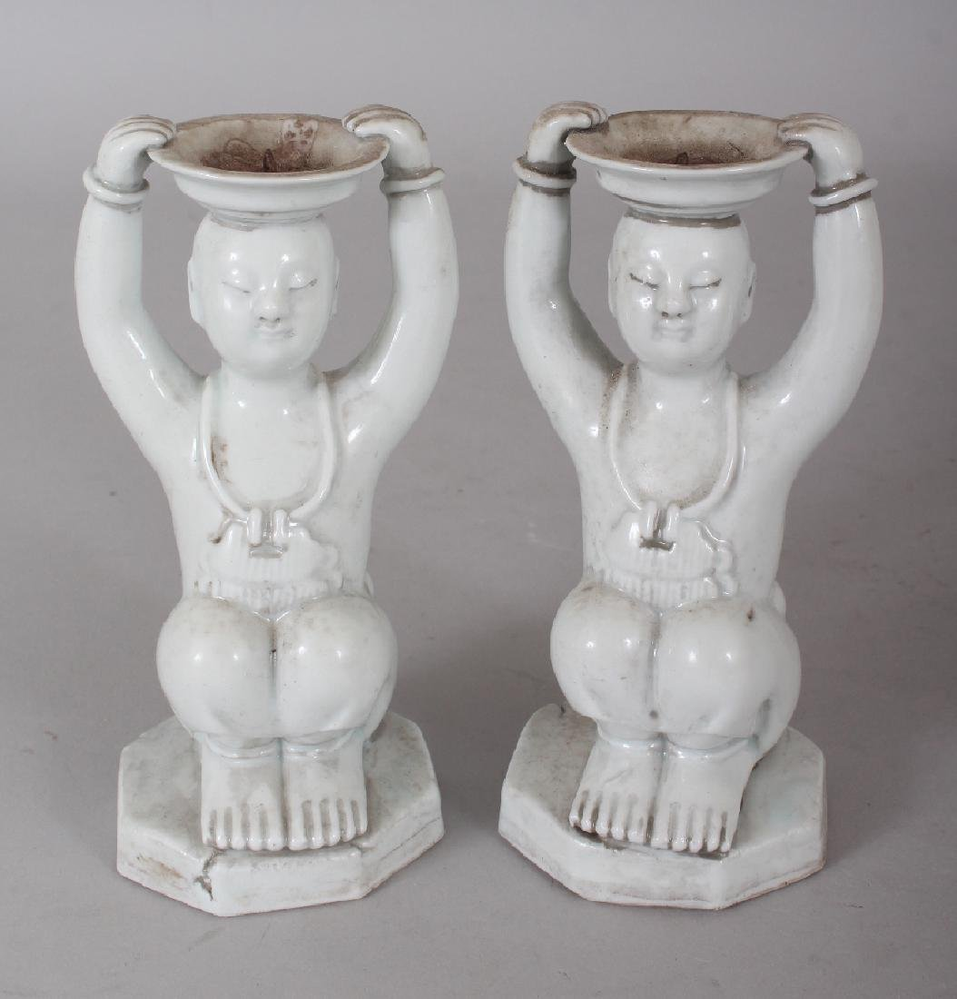 A PAIR OF CHINESE WHITE GLAZED PORCELAIN CANDLESTICKS,