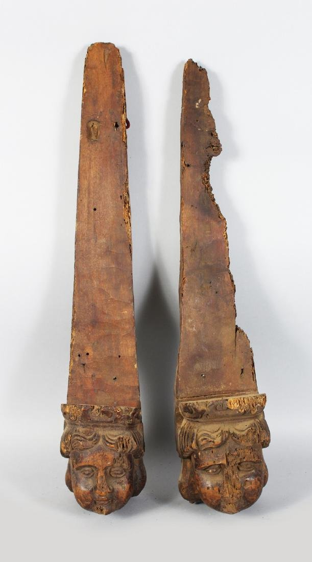 A PAIR OF EARLY CARVED WOOD BRACKETS with carved heads.