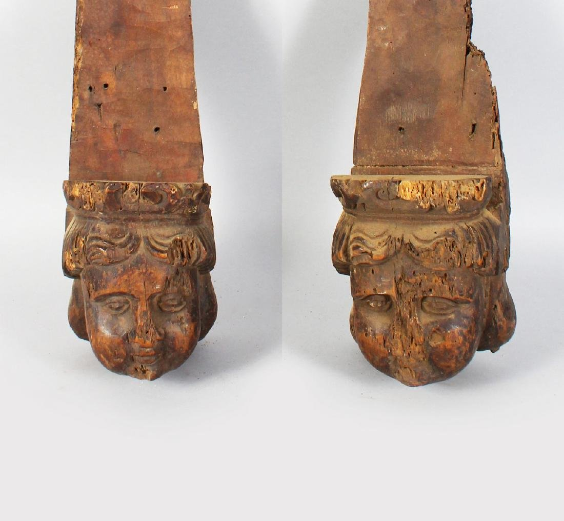 A PAIR OF EARLY CARVED WOOD BRACKETS with carved heads. - 2