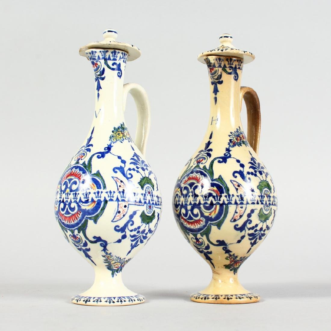 A SMALL PAIR OF FRENCH POTTERY OIL BOTTLES AND COVERS.