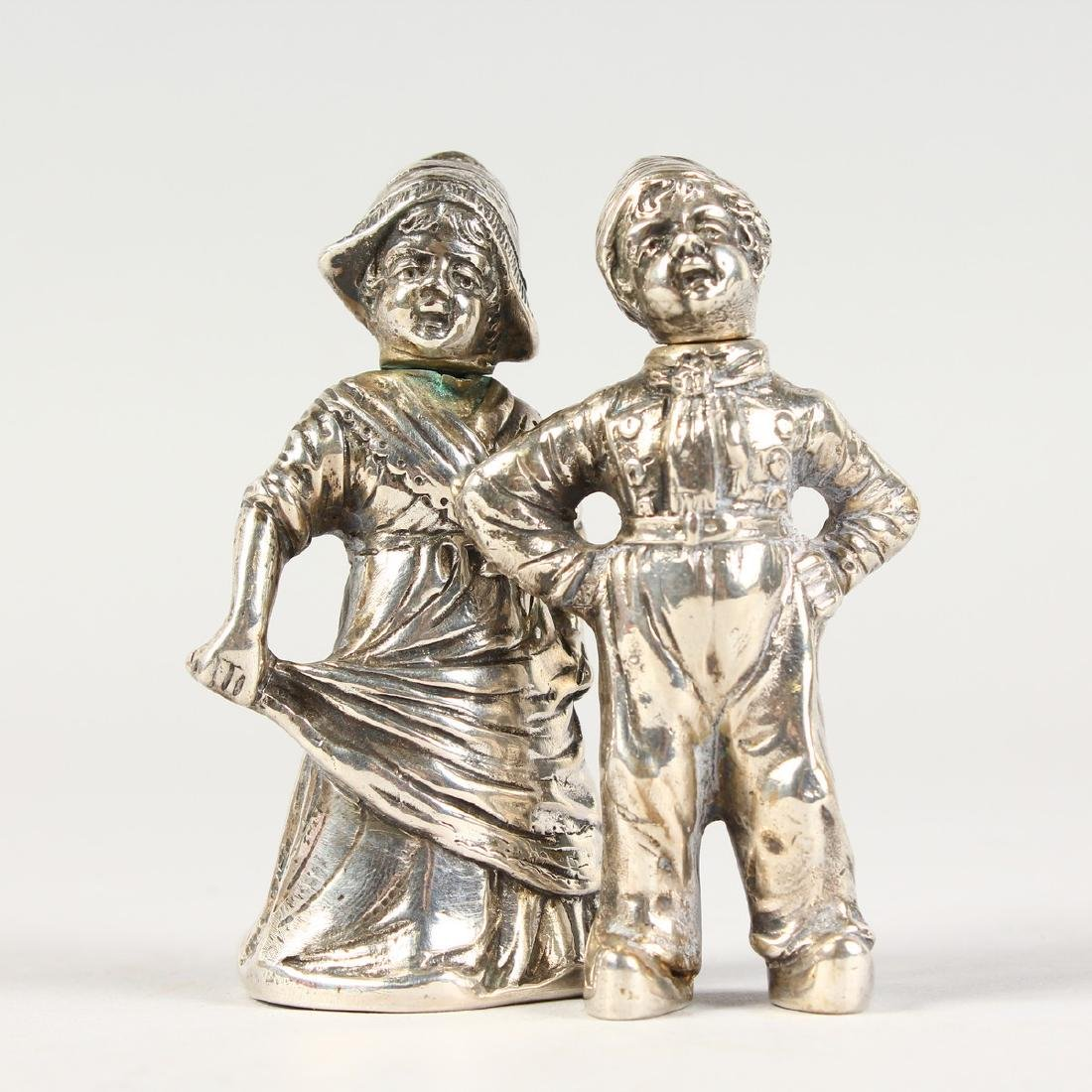 A PAIR OF SILVER DUTCH BOY AND GIRL SALT AND PEPPERS.