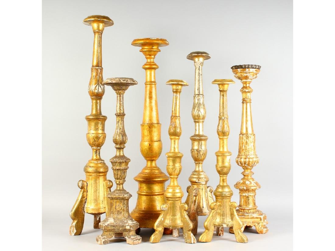 SEVEN VARIOUS ITALIAN CARVED AND GILDED PRICKET