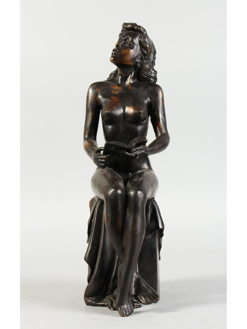 A BRONZE NUDE, sitting on a plinth reading a book.