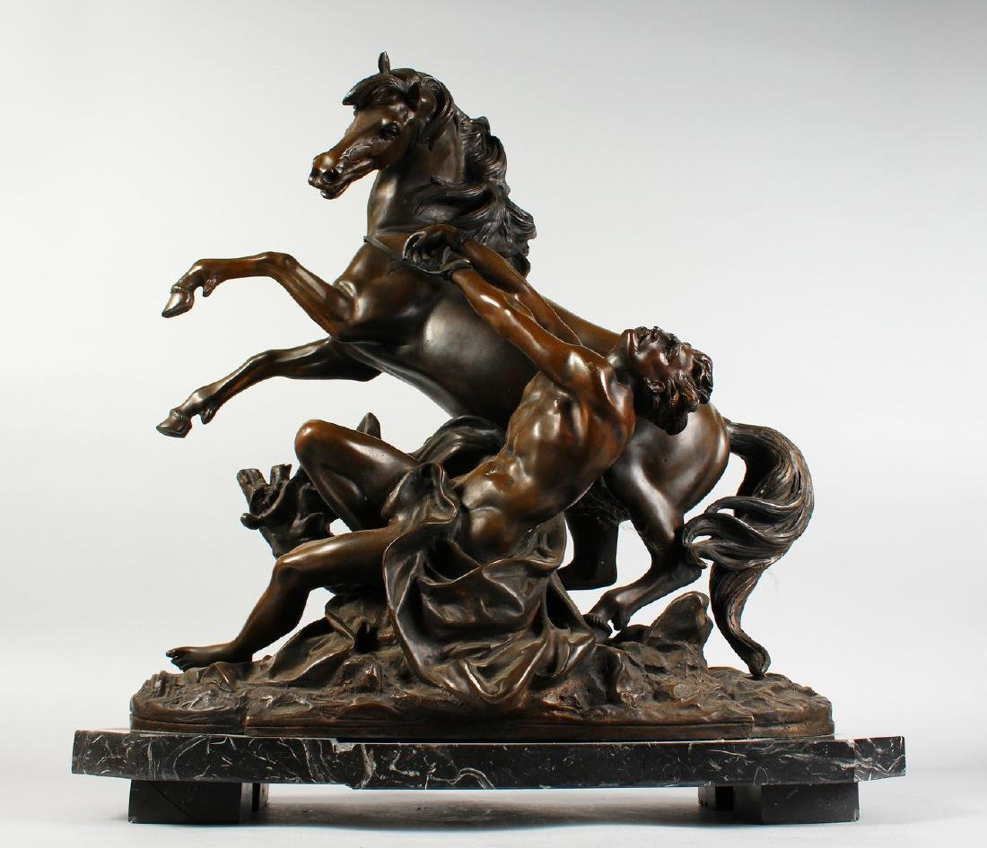 A LARGE BRONZE GROUP OF A YOUNG MAN TRYING TO RESTRAIN