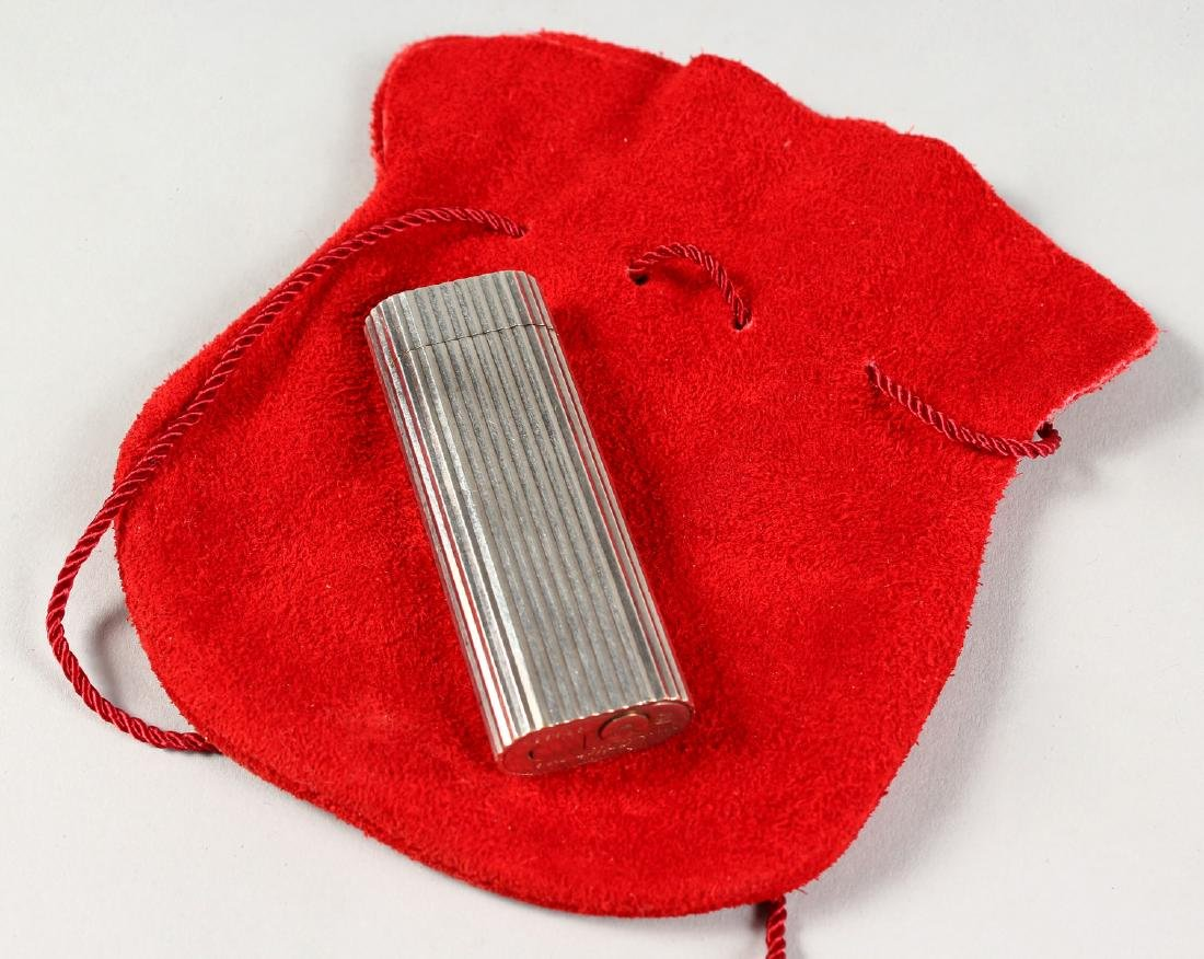 A CARTIER LIGHTER in a red pouch.