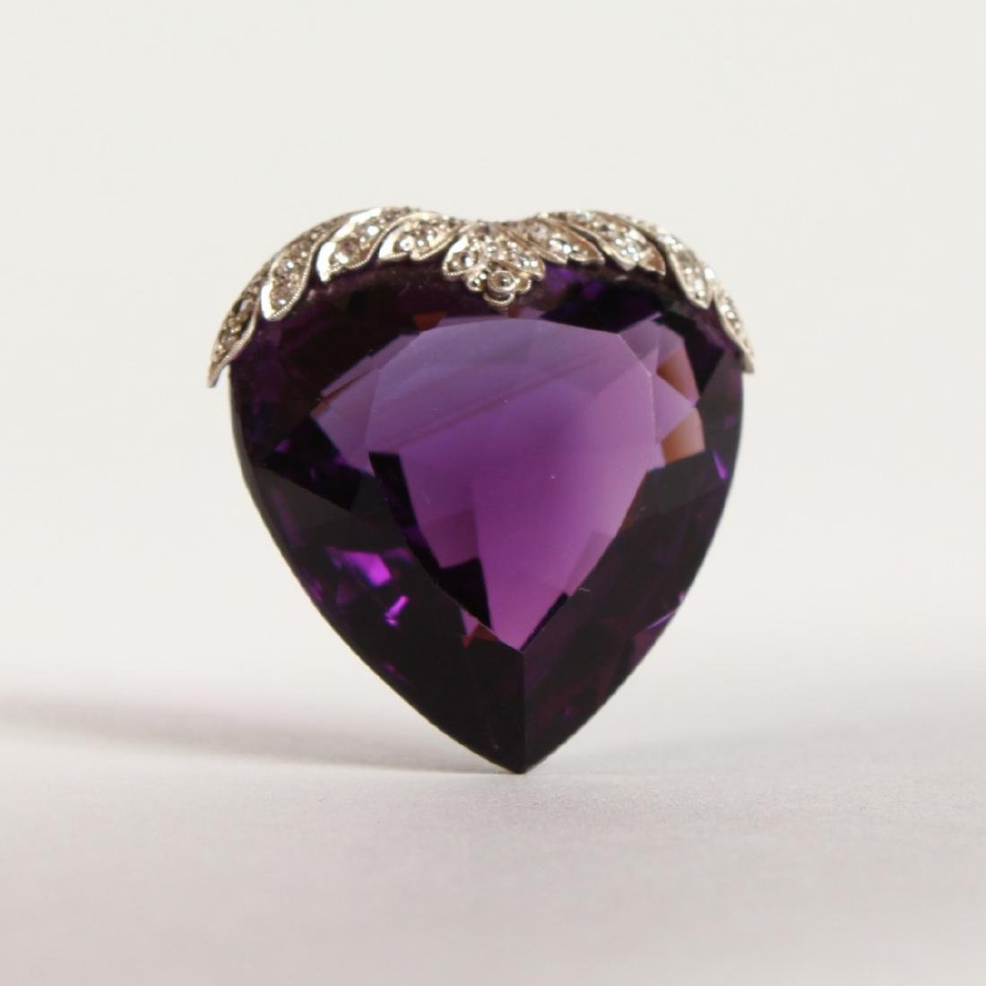 A LARGE HEART SHAPED DIAMOND MOUNTED AMETHYST PENDANT.