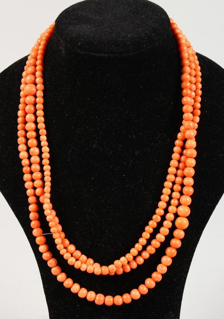 A LONG CORAL SINGLE STONE NECKLACE.
