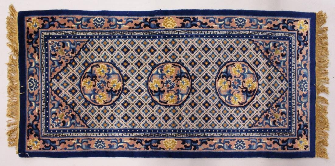 A CHINESE RUG, with three central motifs and blue
