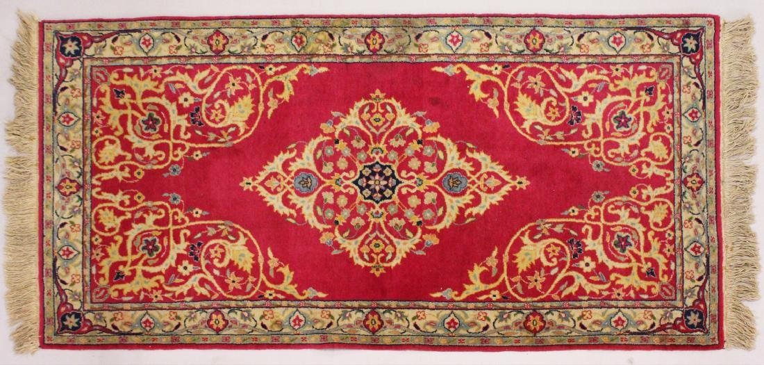 A PERSIAN RUNNER RUG, with central ground, on a rose