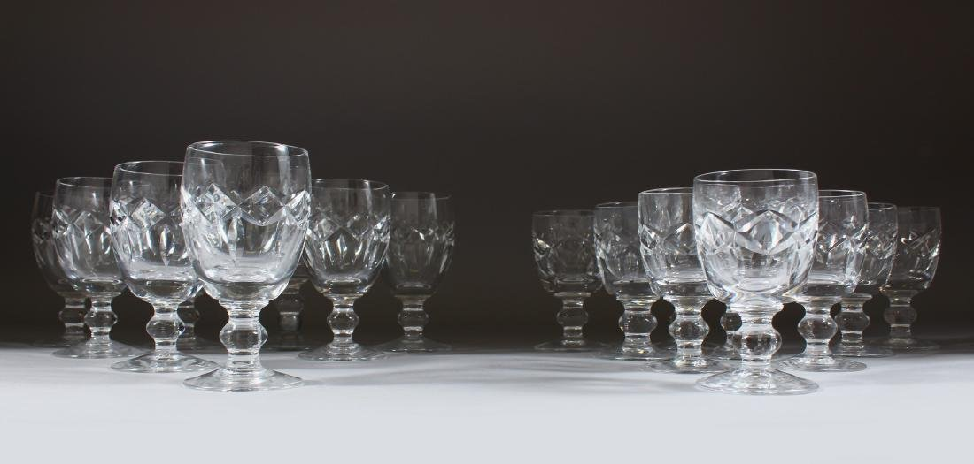 A SET OF EIGHT CUT GLASS WINE GLASSES and nine smaller