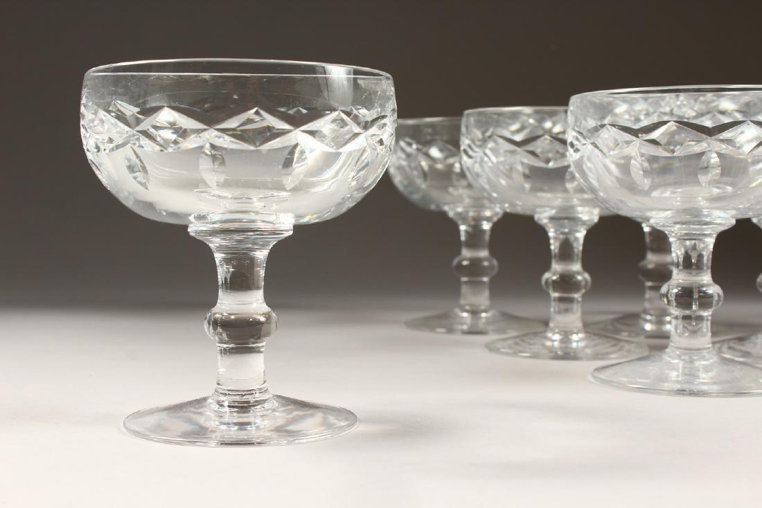 A SET OF TEN CUT GLASS CHAMPAGNE GLASSES.