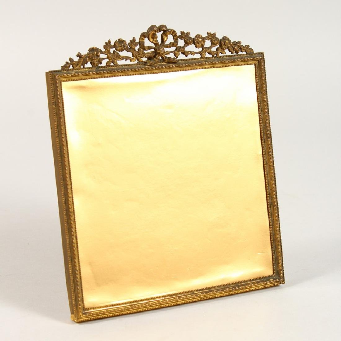 AN ORMOLU PICTURE FRAME, with ribbon and floral