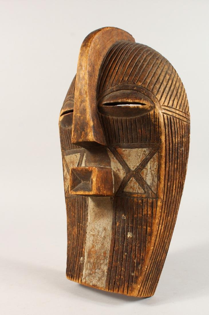 A CASED WOOD TRIBAL MASK, with incised and painted