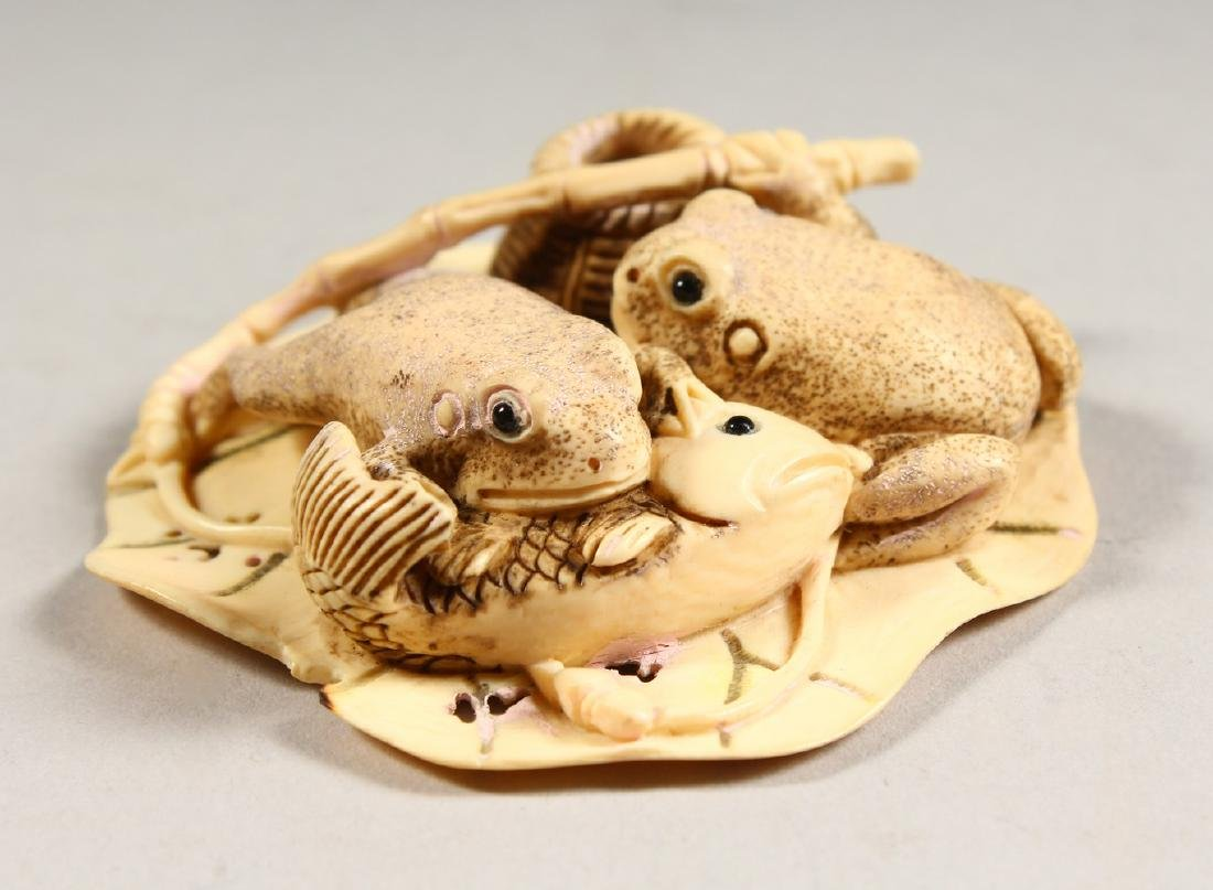 A CARVED BONE GROUP OF TWO FROGS, eating a fish.
