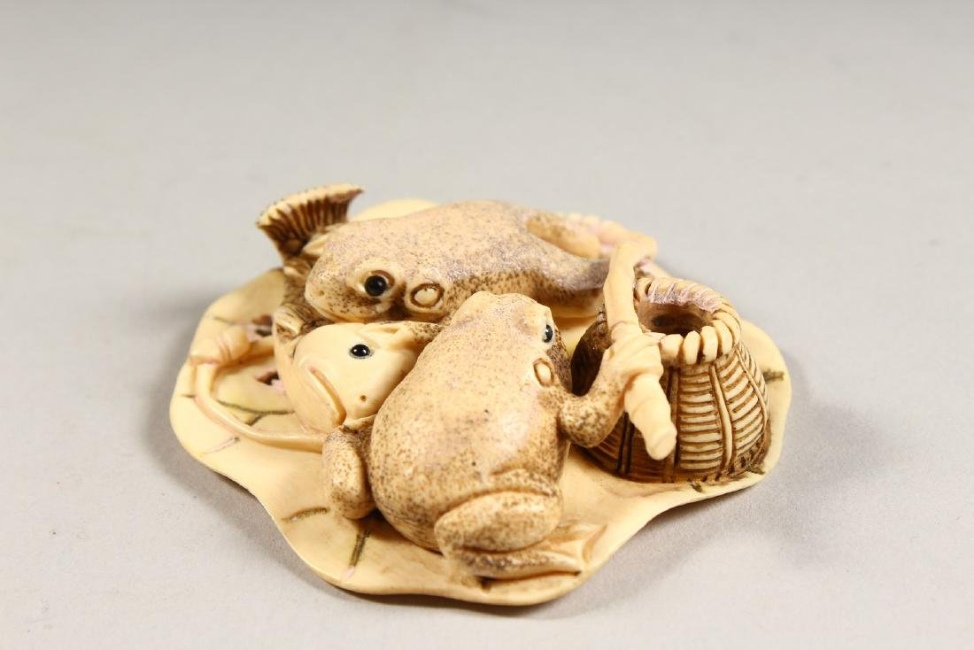 A CARVED BONE GROUP OF TWO FROGS, eating a fish. - 2