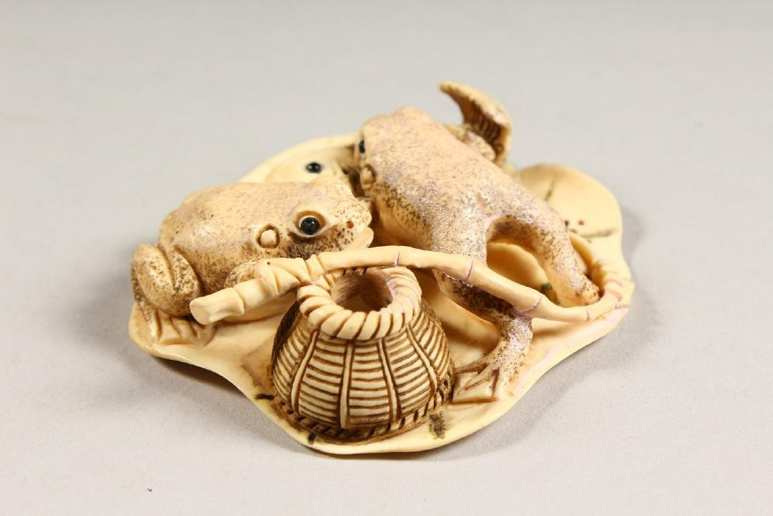 A CARVED BONE GROUP OF TWO FROGS, eating a fish. - 3