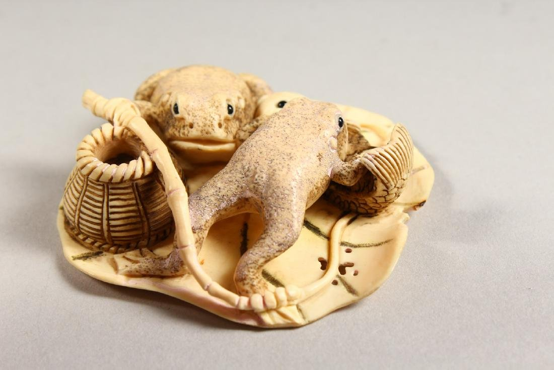 A CARVED BONE GROUP OF TWO FROGS, eating a fish. - 4