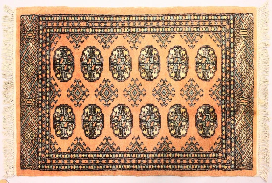 A SMALL BOKHARA RUG, peach ground with two rows of six