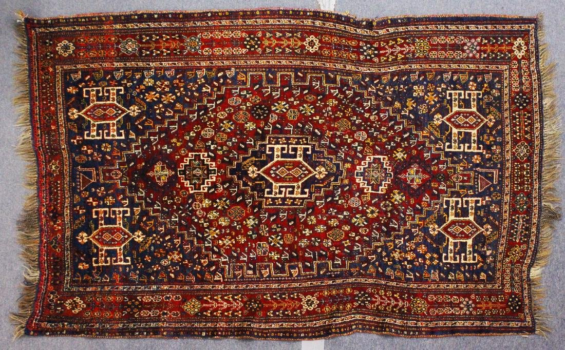 A PERSIAN CARPET, blue and red ground, decorated with