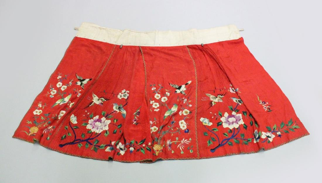 A CHINESE RED EMBROIDERED TEXTILE / SILK SKIRT, with
