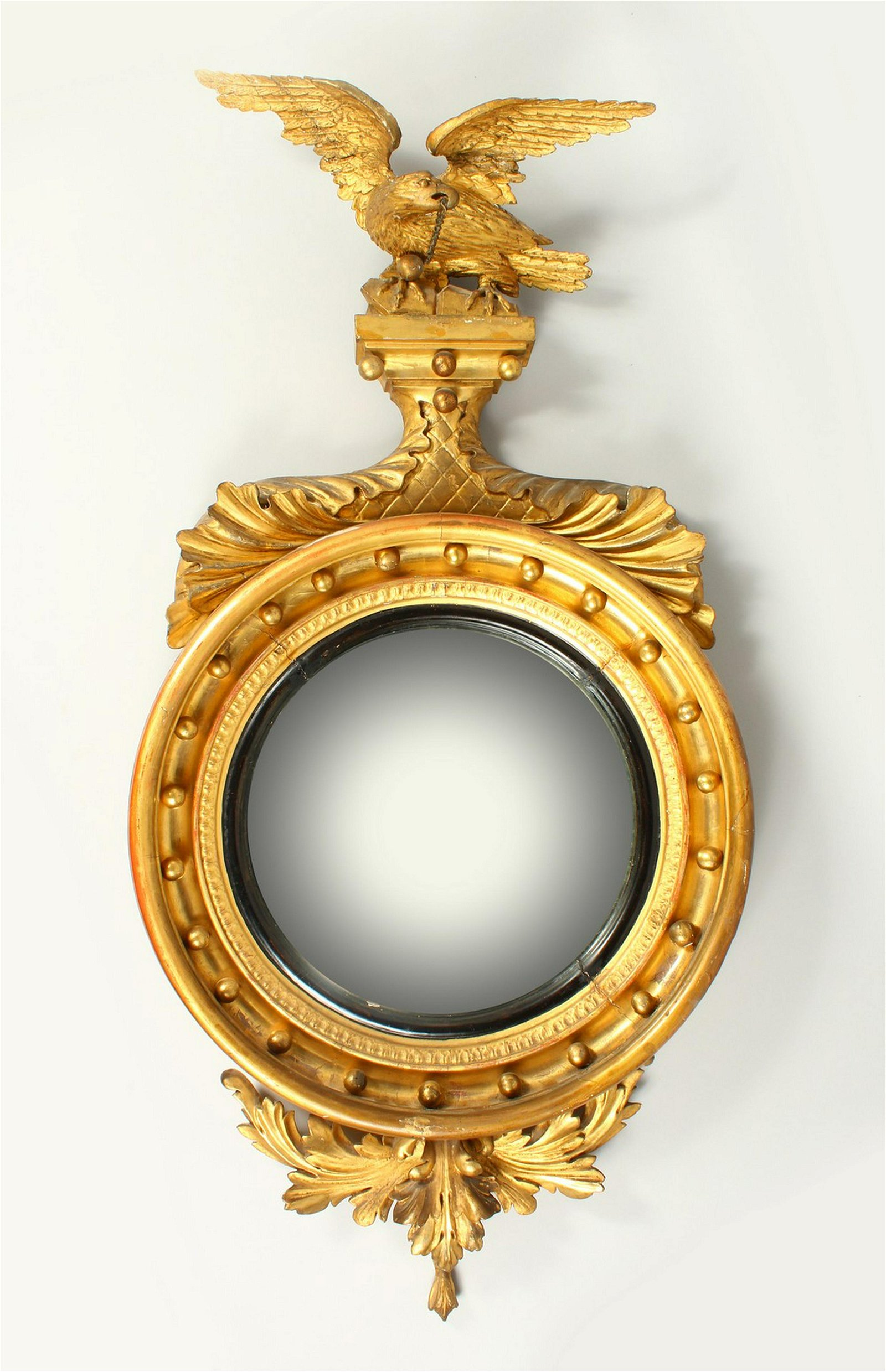 A REGENCY GILTWOOD CONVEX WALL MIRROR, with eagle