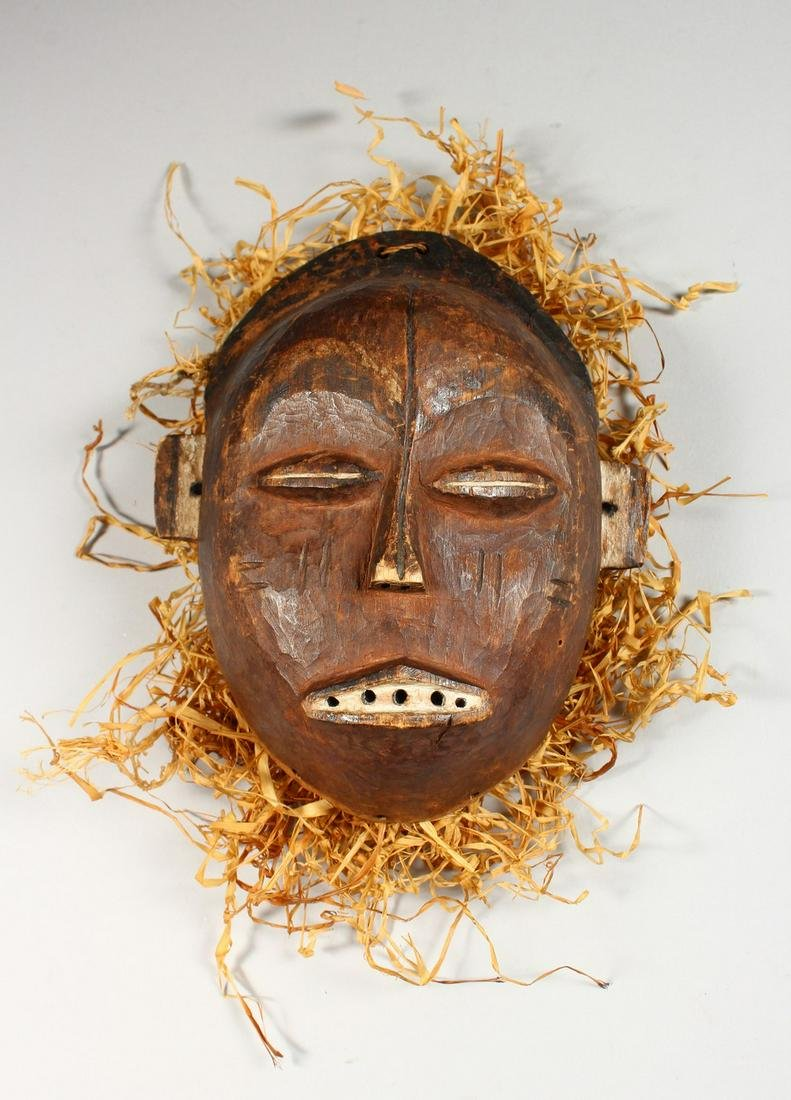 "A CARVED WOOD TRIBAL MASK ""TSHOKWE LWENA SHABA""."