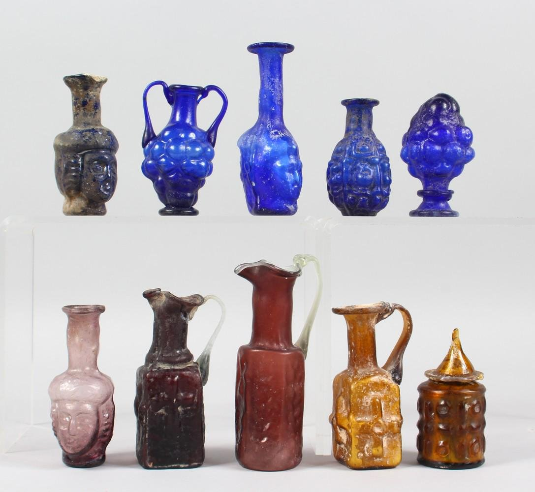A COLLECTION OF ROMAN GLASS BOTTLES, some with moulded