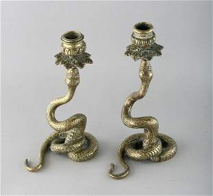 A PAIR OF BRASS SERPENT CANDLESTICKS.  8.5ins high.