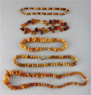 FIVE VARIOUS AMBER TYPE NECKLACES.