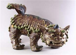 A CHINESE MOULDED POTTERY LION DOG, 48cm long.