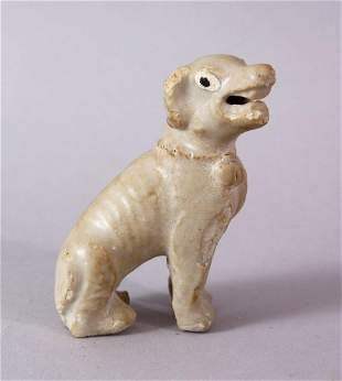 A SMALL CHINESE POTTERY SEATED DOG, 7cm high.