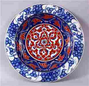 A RARE IZNIK POTTERY PLATE, decorated with blue, white