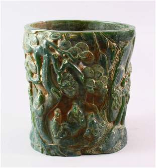 A CHINESE GREEN HARDSTONE BRUSH POT, carved with
