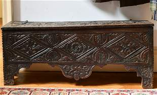 A 17TH CENTURY CARVED OAK SWORD CHEST. 3ft 9ins long x