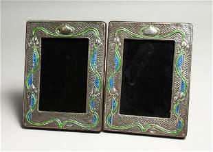 A PAIR OF SILVER AND ENAMEL PHOTOGRAPH FRAMES 7.5ins x