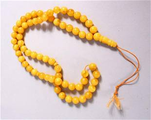 A CHINESE QING DYNASTY CARVED AMBER PRAYER BEADS /