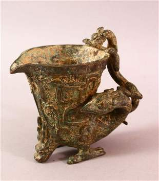 A CHINESE ARCHAIC BRONZE LIBATION CUP, the handle in